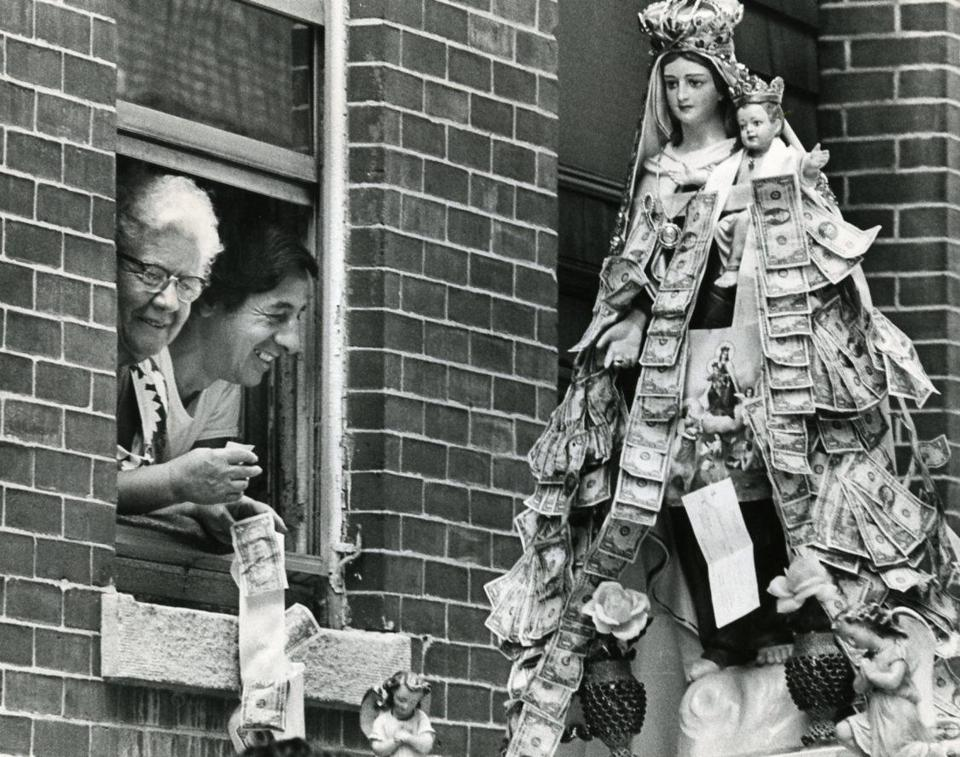 July 14, 1974: Giving donations from their window to the statue of Madonna del Carmine were Josephina Marino and Peter Gerbino. The Feast of Madonna del Carmine was first celebrated in the North End in 1966. While older feasts were initiated by immigrants from Italy, this newest one was started by a small group of young men who were all born in this country and who, said feast chairman, Joseph Santangelo, 22, simply wanted their own celebration.